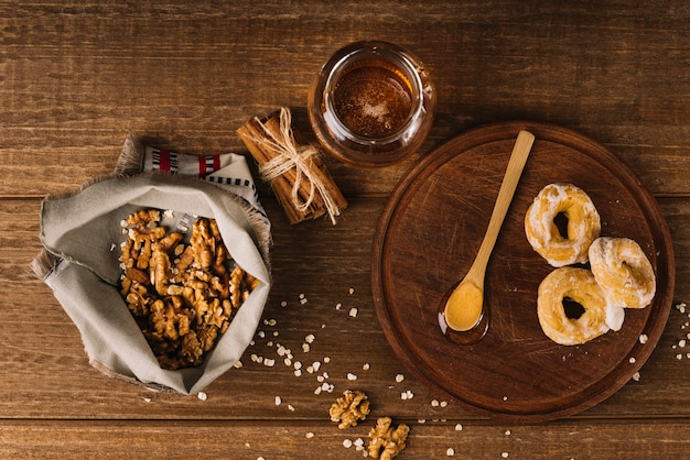 Podniesiony widok miodu; orzech włoski; przyprawy i pączki na powierzchni drewnianych