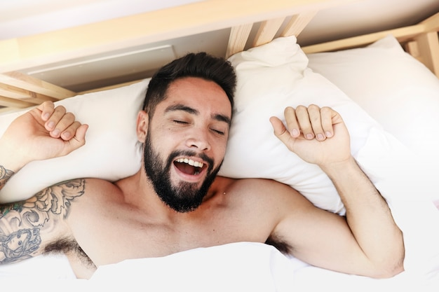 Podniesiony widok młodego mężczyzny budząc się rano