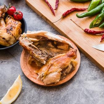 Podniesiony widok na pół zjedzonego pieczonego kurczaka z czerwonymi i zielonymi chilli