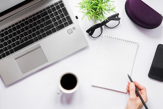 Podniesiony widok osoby ręki writing na ślimakowatym notepad z ołówkiem
