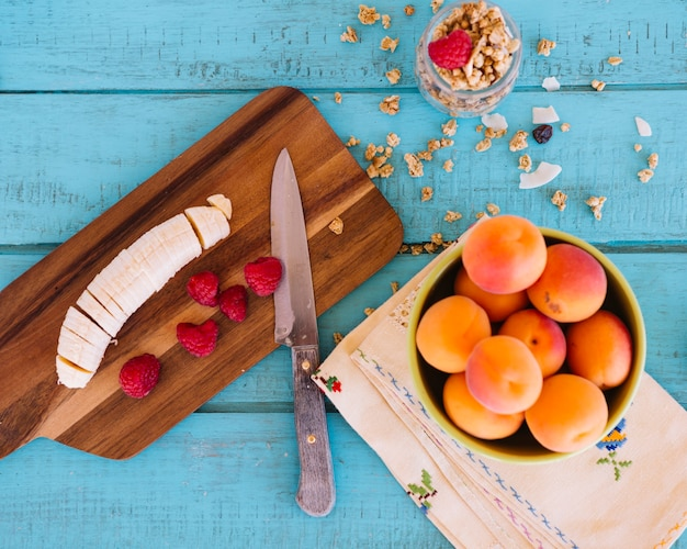 Podniesiony widok plasterków banana; truskawki; brzoskwinia i owies na niebieskim tle drewnianych