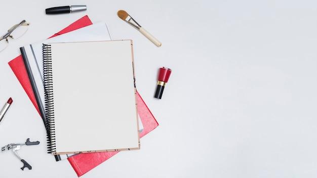 Podniesiony widok pustego notatnika spirali otoczony lakierem do paznokci; pędzel do makijażu; tusz do rzęs; monokl; szminka; i zalotka na białym tle