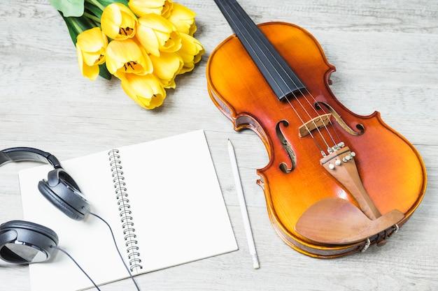 Podniesiony widok pustego notatnika z słuchawek; ołówek; tulipan i klasyczne skrzypce na drewniane tło