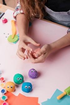 Podniesiony widok ręki trzymającej barwioną glinę do robienia sztuki rzemieślniczej