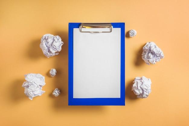 Podniesiony widok schowka z czystym papierze otoczony zmięty papiery
