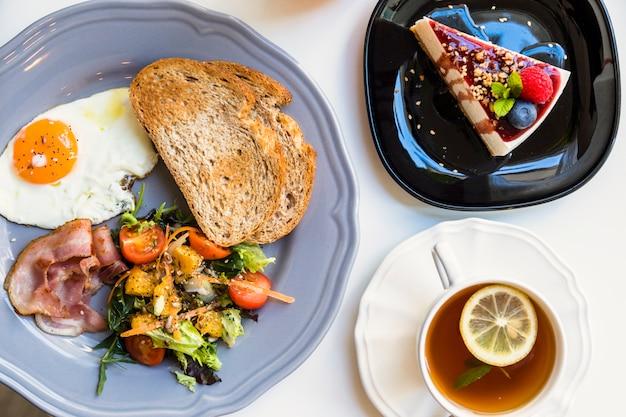 Podniesiony widok smacznego sernika; filiżanka herbaty cytrynowej; toast; sałatka; smażone jajka i bekon na szarym talerzu na białym tle