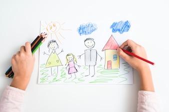 Podniesiony widok strony dziewczyny rysunek rodziny i domu z kolorowym ołówkiem na papierze rysunkowym