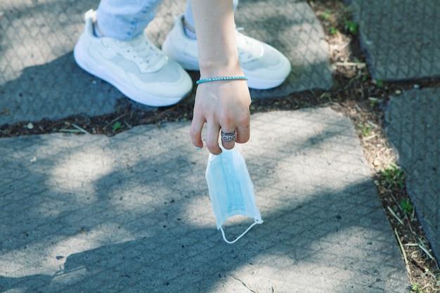 Podnosi maskę medyczną z ziemi na ulicy