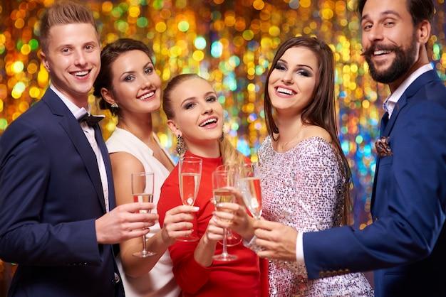 Podnosząc kieliszki szampanem