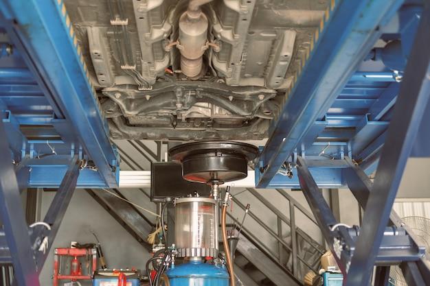 Podnoszenie pojazdu hydraulicznie w celu wymiany oleju silnikowego i kontroli skrzyni biegów. wymiana oleju silnikowego w serwisie samochodowym. konserwacja i kontrola w warsztacie samochodowym.