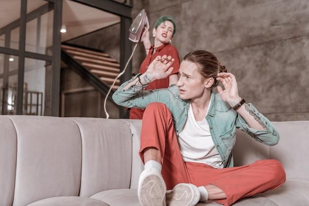 Podnoszenie ręki przeciw. zielonowłosa kobieta czuje się agresywnie, trzymając żelazną rękę podnoszącą rękę na swoim mężczyźnie