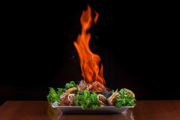 Podpal mięso w glinianej misce. mięso z ogniem na talerzu z grillowanymi warzywami, kebab w pita ozdobiony ziołami.