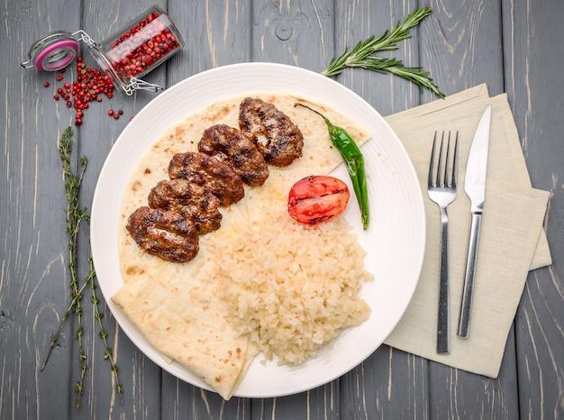 Podpalający mięso, biały ryż i warzywa na drewnianym stole