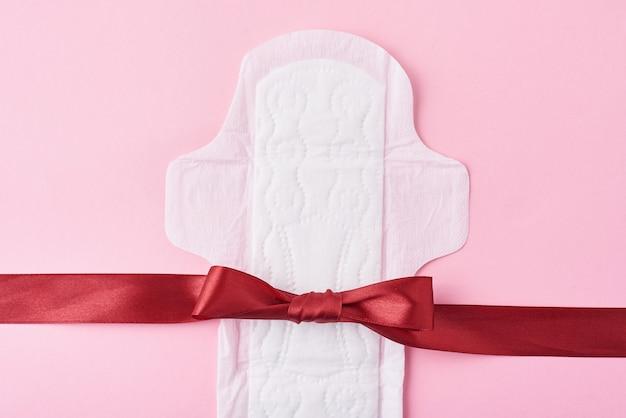 Podpaska higieniczna i czerwona wstążka na różowej powierzchni