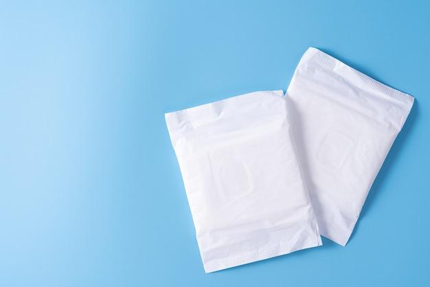 Podpaska higieniczna, podpaska higieniczna na niebieskim tle. miesiączka, higiena kobieca, widok z góry.