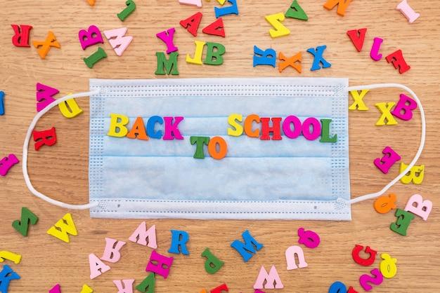 Podpis z powrotem do szkoły jest wyłożony kolorowymi literami na masce ochronnej.