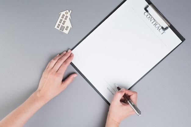 Podpisanie ludzkiej ręki na papierze umowy w pobliżu wycinanka domu papieru na szarym tle