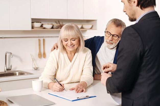 Podpisanie naszej umowy. uśmiechający się uroczy pozytywny starsza kobieta siedzi w domu obok męża i ma spotkanie z pośrednikiem podczas podpisywania dokumentów