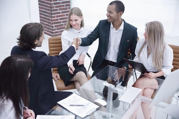 Podpisanie umowy i uścisk dłoni partnerów biznesowych w biurze