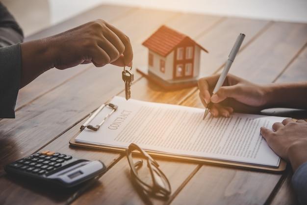Podpisujący podpis pod dokumentem pożyczki na własność domu z własnością agentów nieruchomości. inwestowanie w nieruchomości, hipoteki, ubezpieczenie domu