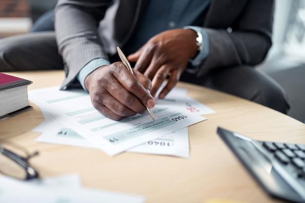 Podpisywanie dokumentów. zbliżenie na ciemnoskórego biznesmena trzymającego długopis i podpisującego dokumenty przy stole