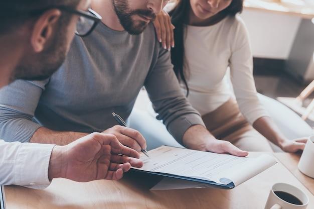Podpisywanie dokumentów. zbliżenie: pewny siebie młody mężczyzna podpisujący jakiś dokument, siedząc razem z żoną i innym mężczyzną wskazującym dokument