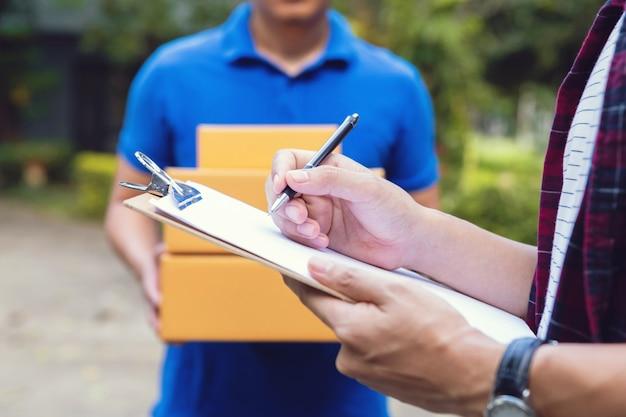 Podpisywanie w celu otrzymania paczki. młody człowiek dostawy trzyma karton, a piękny młody człowiek umieszcza podpis w schowku