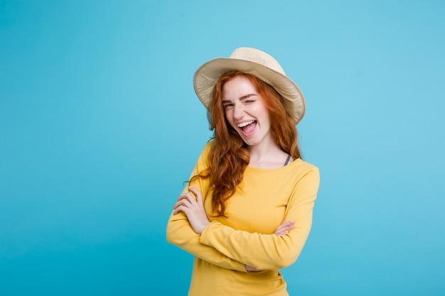 Podrã³å¼e koncepcji - zamknij w górę portret młodych piękne atrakcyjne redhair girl wtih modne kapelusz i okulary uśmiecha się. niebieskie tło pastelowe. skopiuj miejsce.