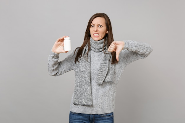 Podrażniona kobieta w szarym swetrze, szalik pokazując kciuk w dół przytrzymaj tabletki tabletki aspiryny w butelce na białym tle na szarym tle. zdrowy styl życia chory chory choroba leczenie koncepcja zimnej pory roku.