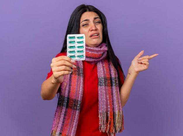 Podrażniona młoda chora kaukaska dziewczyna ubrana w szalik wyciągający paczkę kapsułek w kierunku kamery patrząc na kamerę wskazującą na bok na białym tle na fioletowym tle z miejscem na kopię