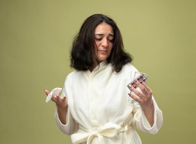 Podrażniona młoda kaukaska chora dziewczyna ubrana w szatę trzymająca paczkę medycznych pigułek szklanka wody i serwetka patrząc na pigułki odizolowane na oliwkowym tle z miejscem na kopię