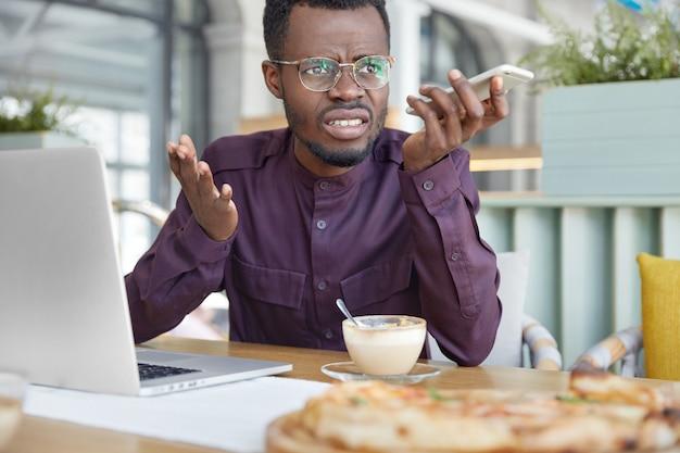 Podrażniony, ciemnoskóry, młody przedsiębiorca mężczyzna przebywający w miejscu pracy czuje się bardzo zestresowany i zły, ponieważ nie jest w stanie wykonać całej pracy