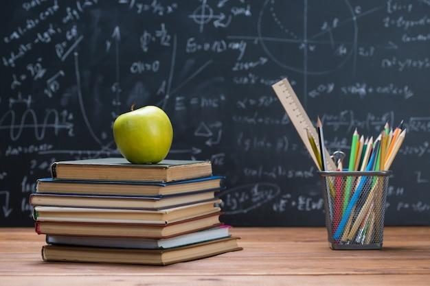 Podręczniki szkolne i artykuły papiernicze na tle drewna i tablicy napisane wzorami matematycznymi i równaniami