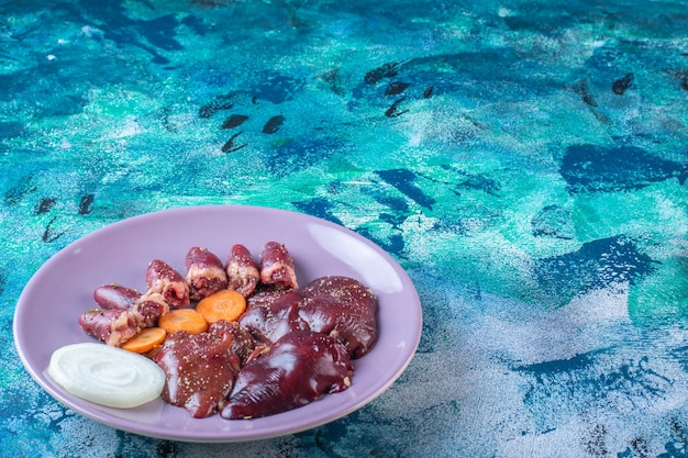 Podroby z kurczaka, marchewka i cebula na talerzu