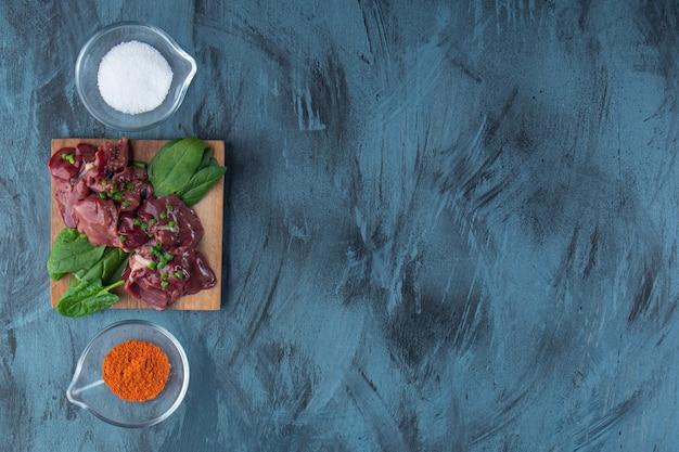 Podroby z kurczaka na desce obok misek na sól i przyprawy, na niebieskim tle.
