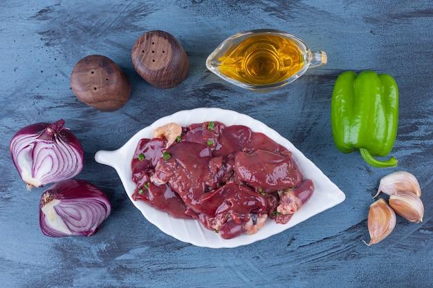 Podroby z kurczaka na półmisku, oliwa, cebula solona, czosnek i pieprz na niebieskiej powierzchni