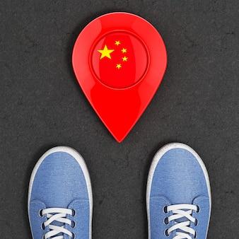 Podróż do koncepcji chin. niebieskie dżinsowe trampki na asfaltowej drodze ze wskaźnikiem mapy i ekstremalnym zbliżeniem widok z góry flaga chin. renderowanie 3d