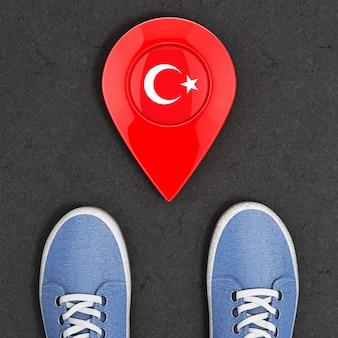 Podróż do koncepcji turcji. niebieskie dżinsowe trampki na asfaltowej drodze ze wskaźnikiem mapy i flagą turcji ekstremalne zbliżenie z góry. renderowanie 3d