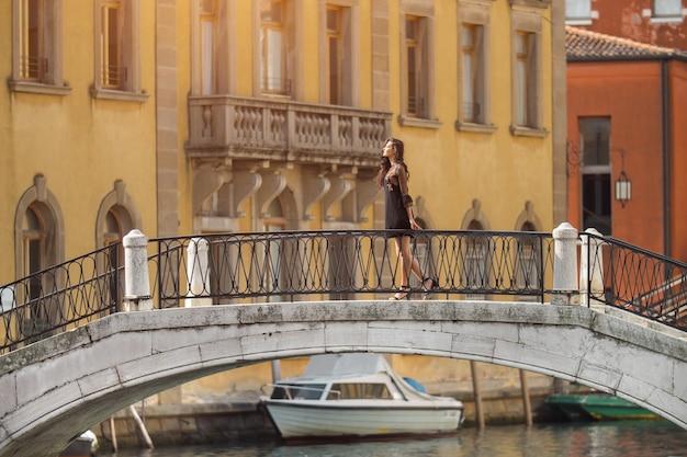 Podróż do włoch. dziewczyna stojąca na moście w wenecji. piękna, dobrze ubrana kobieta, pozowanie na