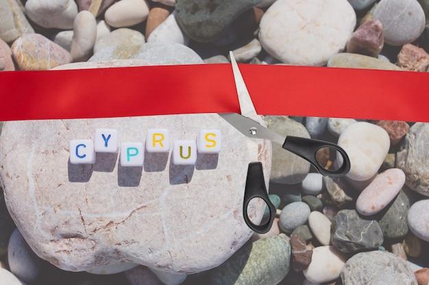 Podróż i turystyka. otwarcie granic, zniesienie ograniczeń w podróżach lotniczych, wycieczki last minute. nożyczki przecinają czerwoną wstążkę z widokiem na morskie kamyki z napisem cypr