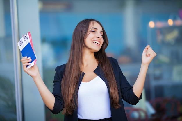 Podróż, kobieta posiadająca dwa bilety lotnicze w paszporcie zagranicznym w pobliżu lotniska