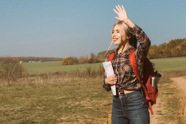 Podróż krajowa kobieta przewodnik macha ręką, wita podróżnych jesienny krajobraz