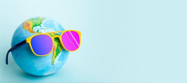 Podróż letnią koncepcję kuli ziemskiej w okularach przeciwsłonecznych na kolorowym tle słoneczne wakacje i turystyka kreatywny pomysł wysokiej jakości zdjęcie