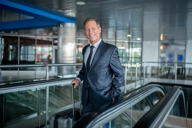 Podróż, lotnisko. atrakcyjny dorosły szczęśliwy mężczyzna w ciemnym garniturze z walizką na schodach ruchomych na lotnisku w optymistycznym nastroju