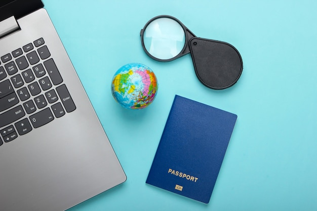 Podróż martwa natura. rezerwacja online. emigracja. laptop, kula ziemska i paszport. akcesoria turystyczne na niebieskim tle. widok z góry