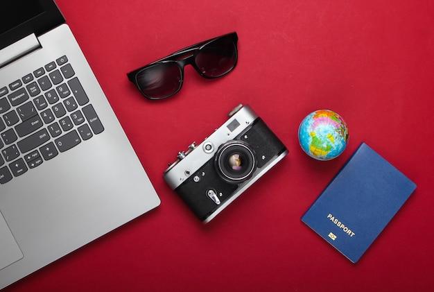 Podróż martwa natura. rezerwacja online. laptop, akcesoria turystyczne na czerwonym tle. podróż dookoła świata