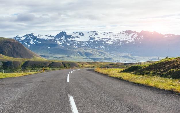 Podróż na islandię. droga w jasny słoneczny górski krajobraz. wulkan vatna pokryty śniegiem i lodem na tne