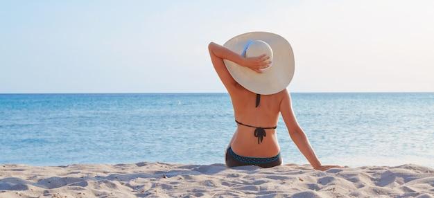Podróż nad morze. dziewczyna w kostiumie kąpielowym i kapeluszu do opalania na plaży.