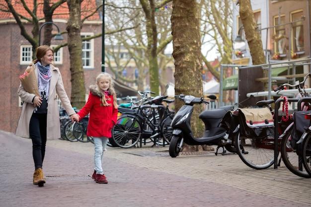 Podróż po europie. szczęśliwa matka i córka spacerują po starym mieście delft, holandia