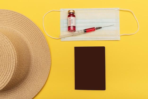 Podróż samolotem w czasie pandemii. na żółtym tle kapelusz, paszport, szczepionka, maska.